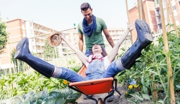 man pushing woman in wheelbarrow through garden