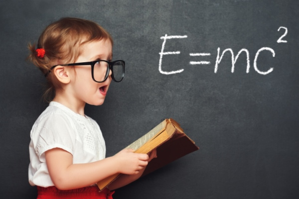 Little girl with glasses in front of blackboard