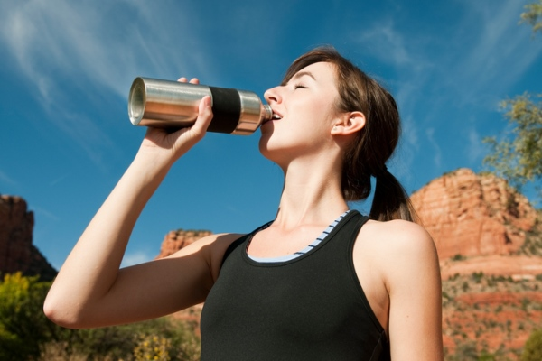 young woman drinking from aluminum water bottle during workout run