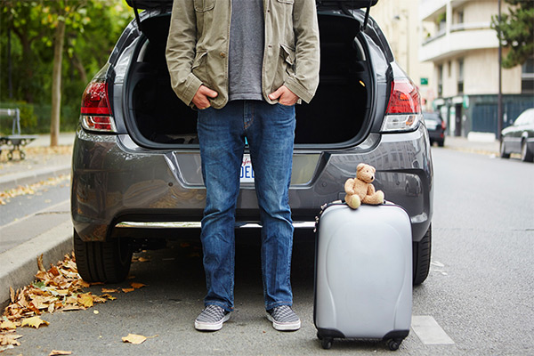 man standing next to car trunk with suitcase