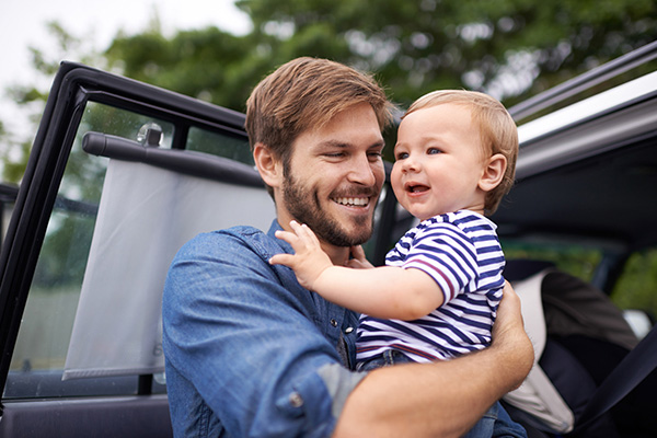 father taking baby son out of car