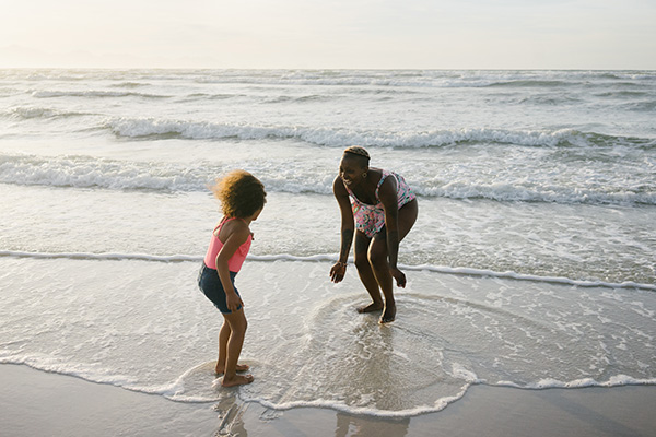 mother and daughter playing at the beach