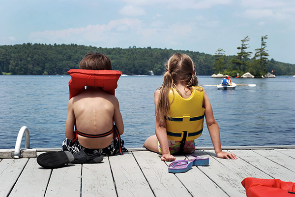 kids sitting on a dock wearing life jackets