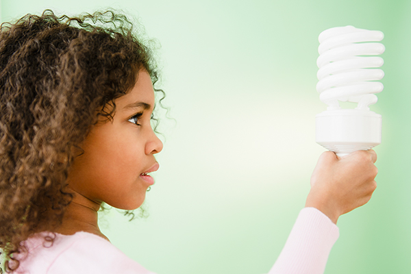 young girl holding energy-saving lightbulb