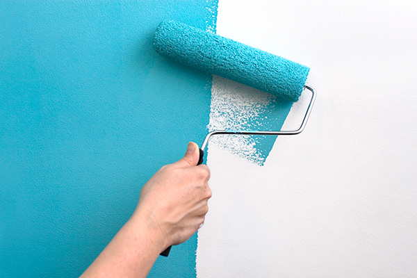 A hand with a paint roller covered in teal blue paint, painting over a white wall
