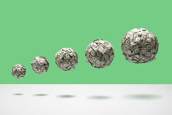 5 balls of US 1 dollar bills of various size in ascending size order, floating in mid air on white floor, green background