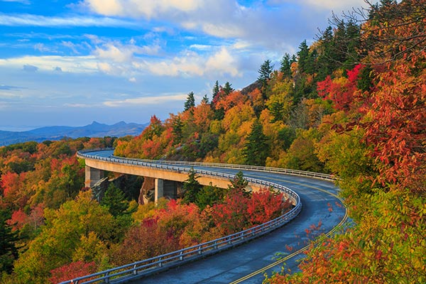Linn Cove Viaduct on the Blue Ridge parkway in the fall season. Road winding through the mountains with autumn colors and blue vibrant morning skies.