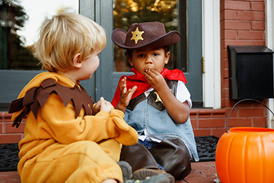 kids eating halloween candy on front porch