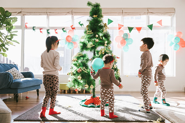 kids playing around a christmas tree