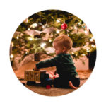 baby playing with toys underneath christmas tree