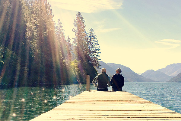 """Friends at the end of a dock on Lake Chelan, Stehekin, North Cascades National Park entrance,Washington , USA"""