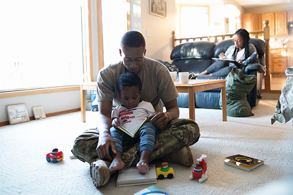 Military father and child reading together