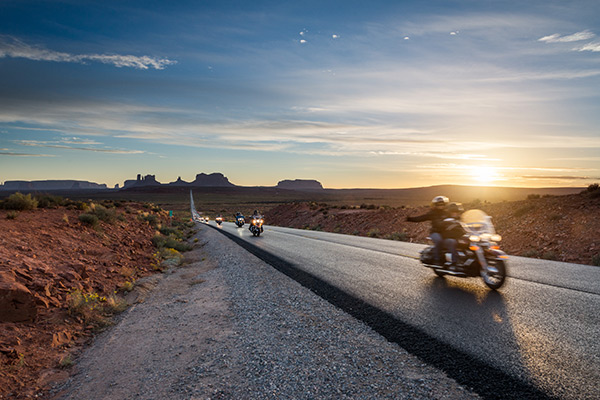 motorcycles riding down a desert road