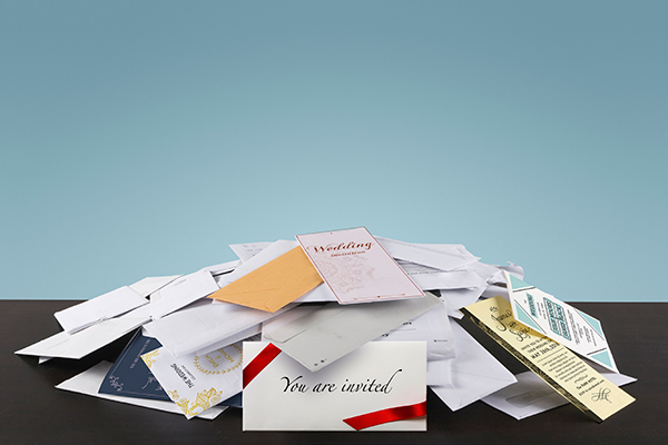 pile of mail with wedding invitation