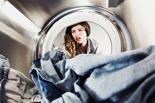 young woman looking into washing machine