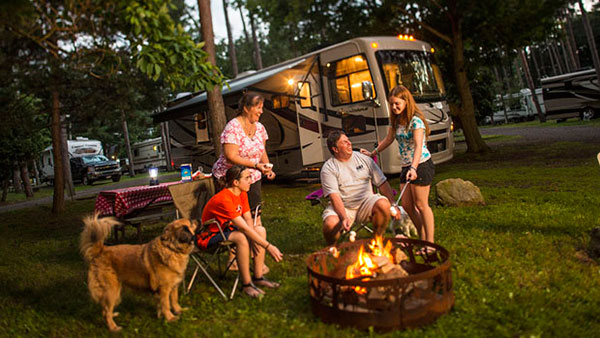Family enjoying their GEICO insured RV at a KOA Campground
