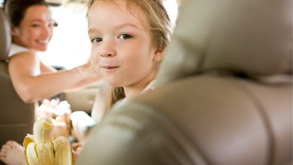 Girl eating banana in car