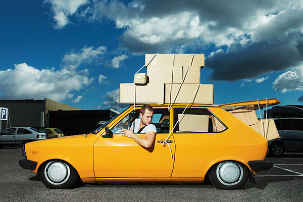 young man driving with boxes tied to the roof of his car