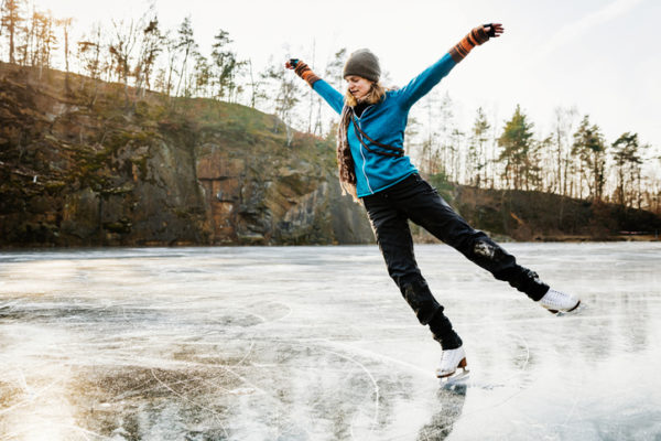 An amateur ice skater posing with her arms in the air while skating on a frozen lake.