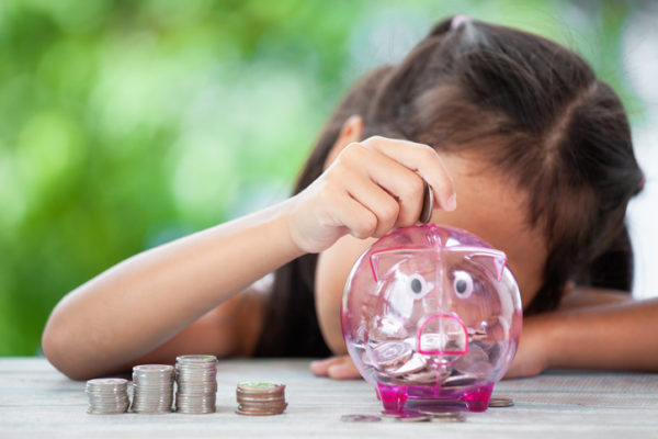 Girl Putting Coin In Piggy Bank At Table
