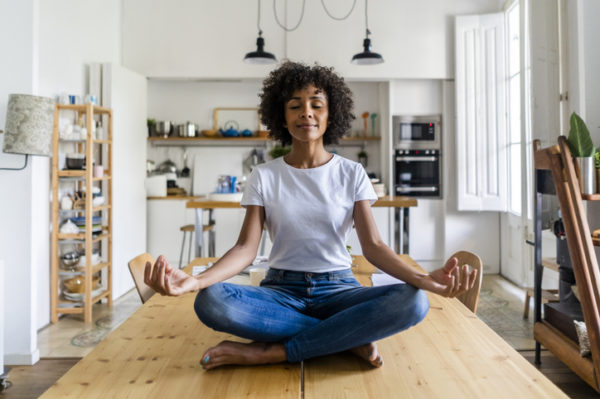 Smiling woman with closed eyes in yoga pose on table at home