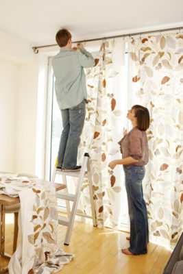 Woman directing man how to hang curtain