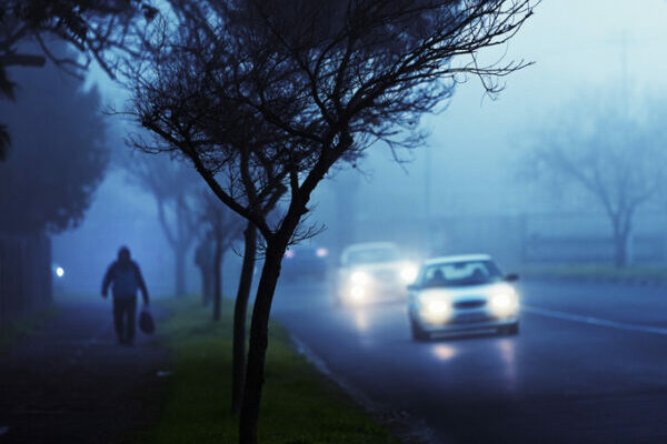 Commuters' cars drive through fog on city street at twilight