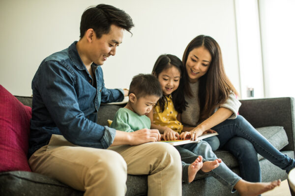Family reading a book with young children at home