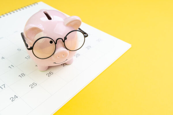 Annual budget allocation, schedule for saving and invest or planning for financial date, smiling pink piggy bank wearing eyeglasses on white clean calendar on solid yellow background with copy space.
