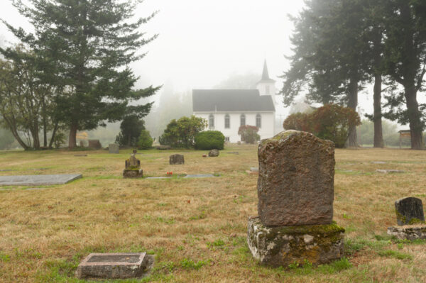 Historic cemetery dating back to the 1800's situated behind a classic white church built in 1908. This foggy morning adds atmosphere.