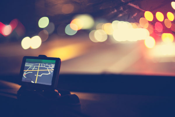 Night shot of GPS navigational system on dashboard of car. Traffic lights are visible through windshield.