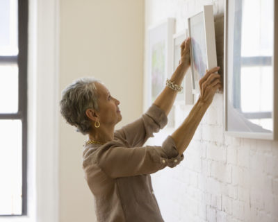 Mixed race woman hanging pictures on wall