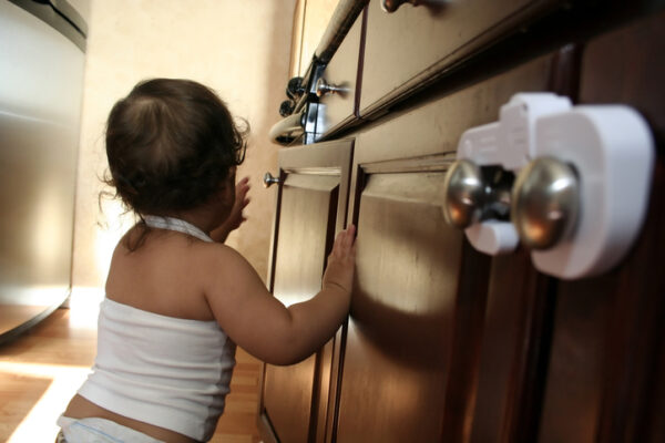 Toddler cruising along the kitchen - part of a series - focus on unsecured cabinet door