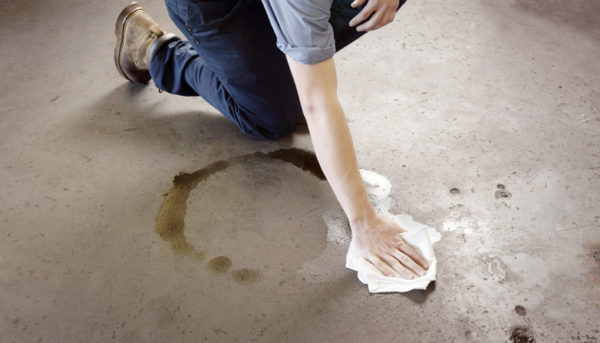 Oil clean-up in a workshop. A man cleaning-up an oil spill on a workshop floor. The man is wearing work boots and mechanic's clothing.