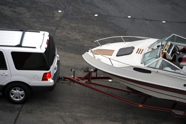 An suv tows a boat