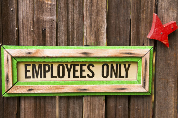 Wooden sign with the words Employees Only.