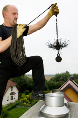 Chimney sweep at work on the roof. Manual worker. Holding up a chain with the broom to clean the chimney. XXXL (Canon Eos 1Ds Mark III)