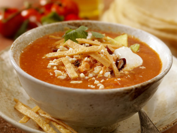 Authentic Mexican Tortilla Soup - Crispy tortilla stripes smothered in a chipotle tomato broth, garnished with chile pasilla, avocado slices, queso fresco (fresh cheese), sour cream, shredded chicken and radish slices. - Photographed on Hasselblad H3D2-39mb Camera