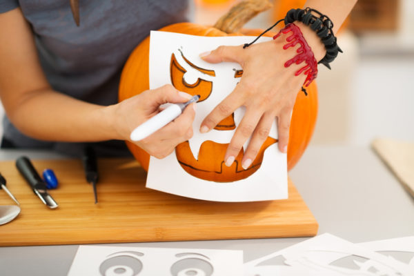 Closeup on woman using stencils to carve big orange pumpkin Jack-O-Lantern for Halloween party. Traditional autumn holiday