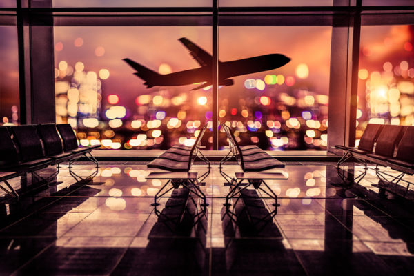 Empty airport lounge shot at night in front of the city skyline with airplane taking off against the bright lit of the city.