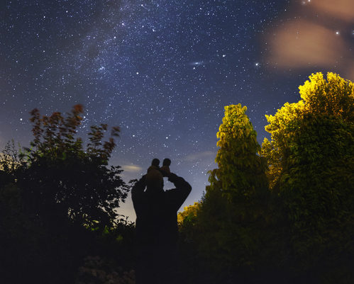 An amateur astronomer observes the Milkyway with binoculars from a rural garden in the southwest of England.