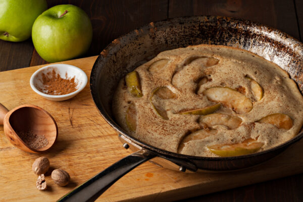 A high angle extreme close up horizontal photograph of a German apple pancake in grandmas well used frying pan. A bowl with ground cinnamon and a small wooden scoop along with ground nutmeg and some whole nutmegs sit by the pan on the cutting board.Two fresh green granny smith apple can be seen in the background.