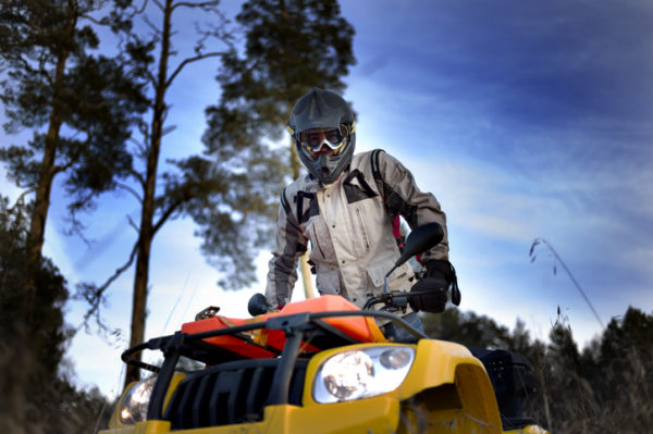 Horizontal close-up of a man in helmet and safety goggles looking into the camera while sitting on quad bike against vivid blue sky.