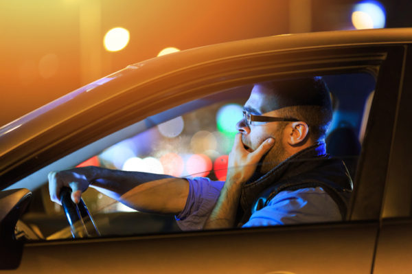 Side view of young man with eyeglasses sitting inside of his car and yawning. One hand on mouth. Bright lights at background.