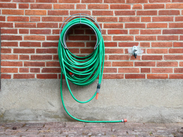 Green Garden Water Hose Hanging on Red Brickwall. Not connected to Water Tap.