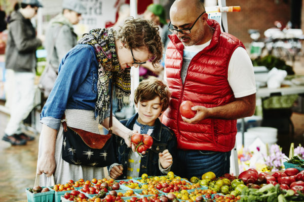 Family examining organic tomatoes while shopping at farmers market