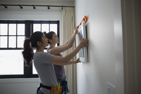 two women hanging picture frame on wall