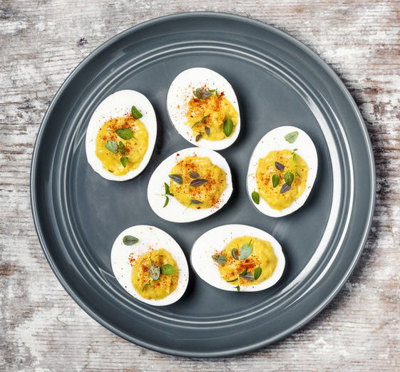A plate of deviled eggs on wooden background