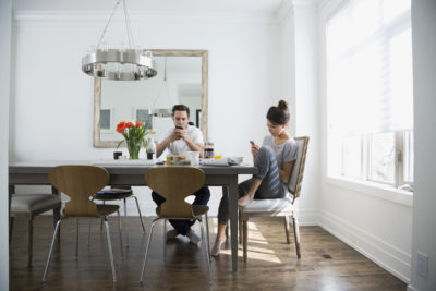 Couple texting with cell phones at breakfast dining table