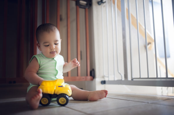 Baby boy plays with his yellow toy truck